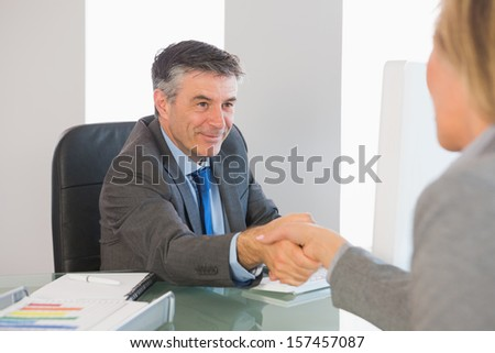 Pleased mature businessman shaking the hand of a blonde interviewee in office - stock photo