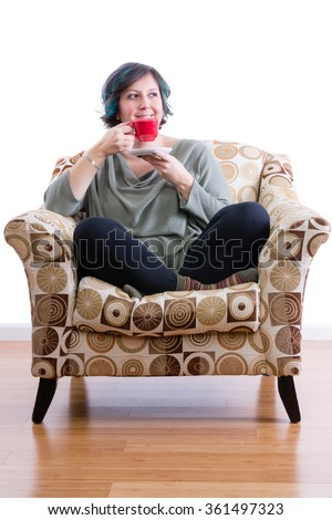 Pleased middle-aged woman at home sitting comfortably in sofa chair enjoying her morning coffee - stock photo