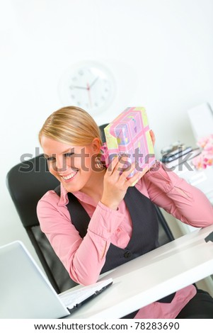 Pleased modern business woman sitting at office desk and holding gifts in hands - stock photo