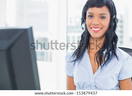 Pleased operator looking at camera in office - stock photo