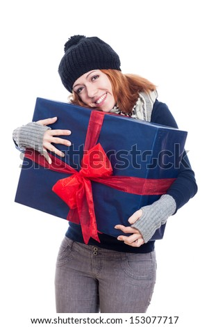 Pleased winter woman holding big present, isolated on white background. - stock photo