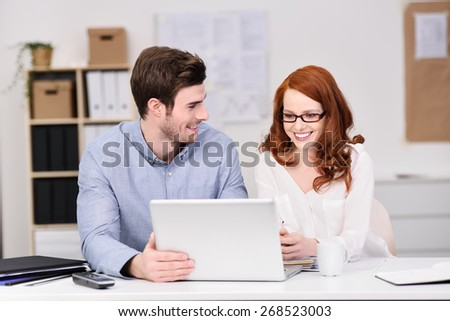 Pleased young business team working together at a laptop smiling as they see their project come to fruition, man and woman - stock photo