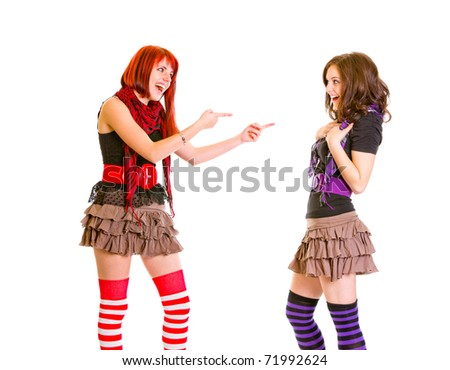 Pleased young girl pointing fingers at her amazed girlfriend isolated on white - stock photo