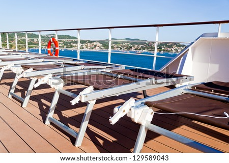 Pleasing and relaxing view from the deck on a cruise ship for summer vacation, with chairs. This is good to advertise vacation and holidays on cruises. - stock photo