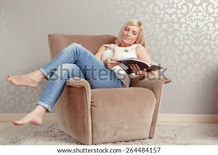 Pleasure of reading. Attractive mature woman in casual clothes settled in the armchair with the magazine in her hands - stock photo