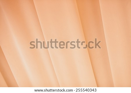 Pleated curtain in warm and peachy tones - stock photo