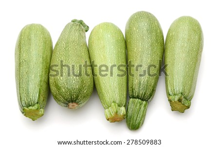 plenty of fresh zucchini in row on white background  - stock photo
