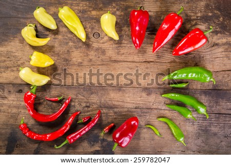 Plenty of red, yellow and green peppers on wooden background with empty space - stock photo