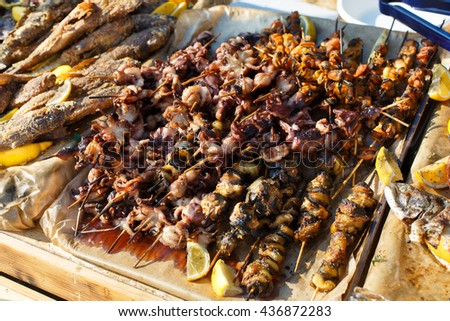 Plenty of seafood, fish, octopus, mussels grilled at barbecue. Seafood bbq outdoors at picnic, party. Street food, seafood takeaway at big tray. Grill at bamboo sticks. - stock photo