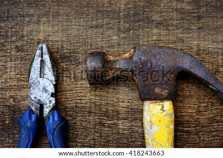 pliers and hummer on wood background - stock photo