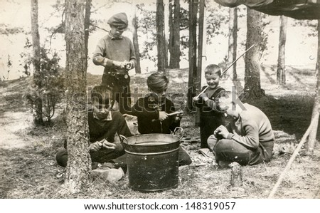 PLOCICZNO, POLAND, CIRCA 1957 - vintage photo of group of scouts peeling potatoes during a summer camp, Plociczno, Poland, circa 1957 - stock photo