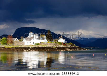 Plockton Village in The Highlands Of Scotland with mountains in the background and reflections on Loch Carron - stock photo