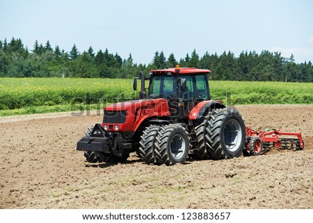Ploughing heavy tractor during cultivation agriculture works at field with plough - stock photo