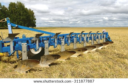 plow on the field ready to work - stock photo