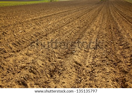 Plowed brown agricultural soil - stock photo