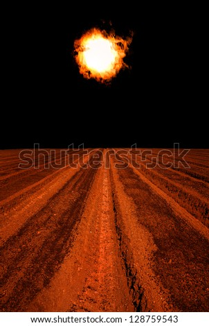 Plowed earth under the solar magnetic storm - stock photo