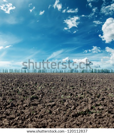 plowed field under dramatic sky - stock photo