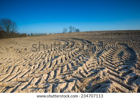 plowed field with tractor traces under blue sky - stock photo