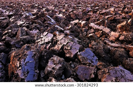 plowed soil. spring field. sunset over ploughed field.  - stock photo