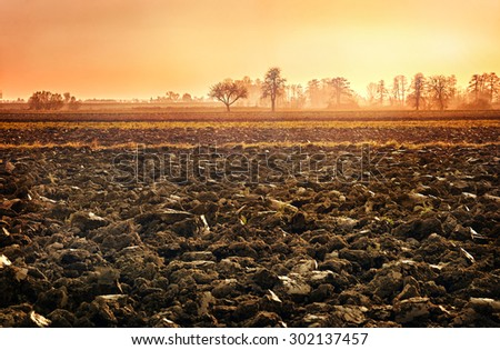plowed soil. spring field. sunset over ploughed field. Countryside landscape - stock photo