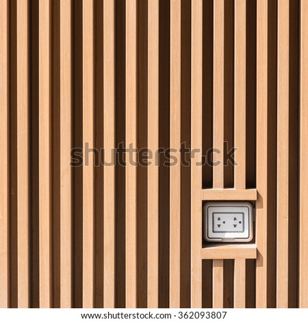 Plug socket on light brown wooden wall pattern at outdoor installation - stock photo