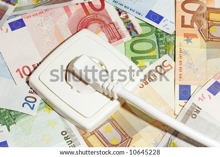 Plugged power cable isolated on a money background. - stock photo