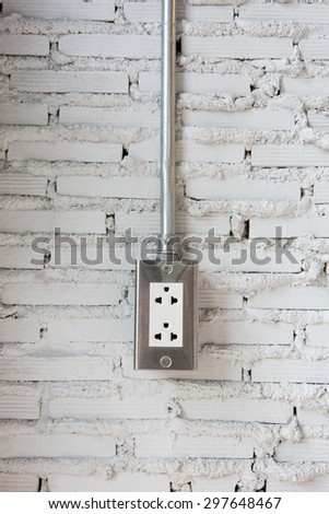 Plugged power cord in wall socket on White plaster walls - stock photo