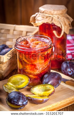 Plum compote with fresh fruit on a wooden table. - stock photo