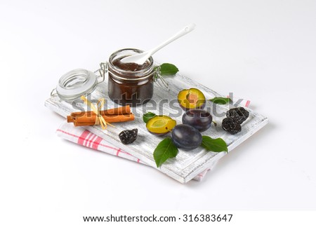 plum jam, cinnamon, fresh and dried plums on wooden cutting board - stock photo