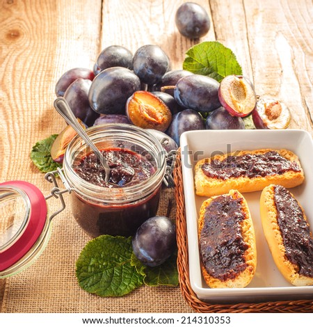 Plum jam on toasted bread with plums in the background - stock photo