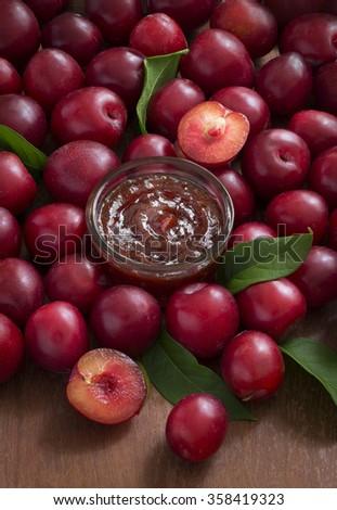 Plum jam with fresh plum on wooden background. - stock photo