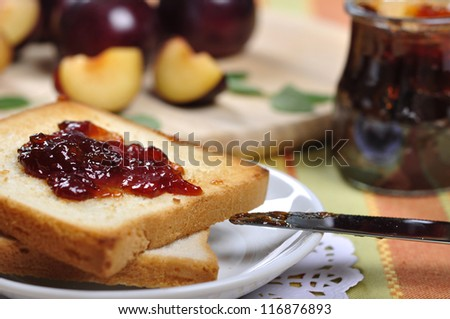 Plum jam with toast on white plate and fresh ripe plums. Small shallow dof. - stock photo