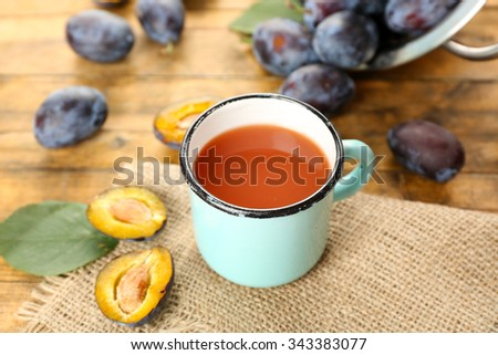 Plum Juice in mug with fresh fruits - stock photo