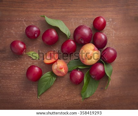 Plum on wooden background. Overhead view. - stock photo