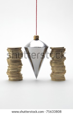 Plumb bob with coin stacks on white background - stock photo