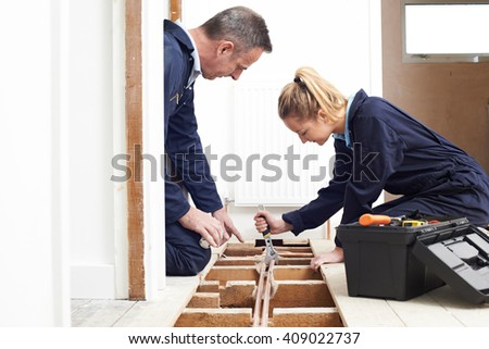 Plumber And Apprentice Fitting Central Heating - stock photo
