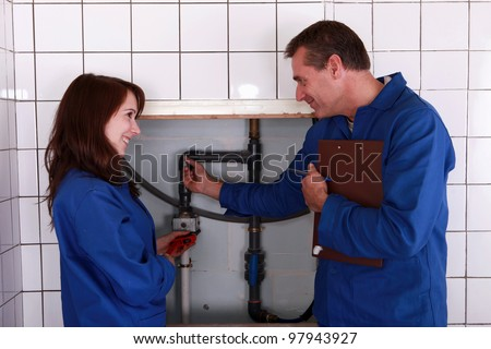 plumber and his apprentice examining the pipes - stock photo