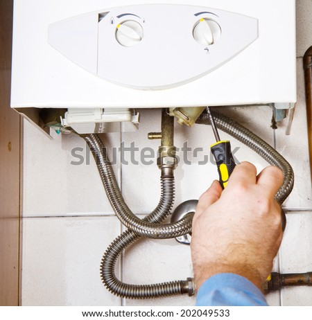 Plumber at work. Servicing gas boiler  - stock photo