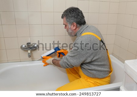 Plumber caulking bath tube with silicone glue using cartridge - stock photo
