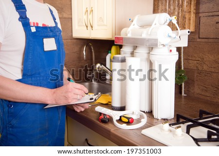 plumber change the water filter - stock photo