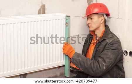 plumber check bubble level horizontal installation radiator - stock photo