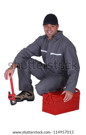 Plumber crouching by his tool box - stock photo