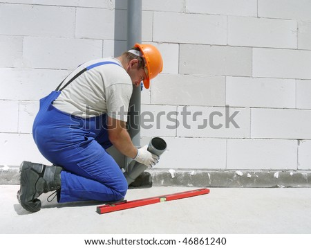 Plumber fitting pvc sewage pipes inside newly built house - stock photo