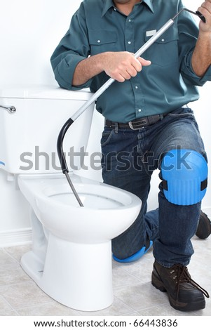 Plumber fixing a flush toilet - stock photo