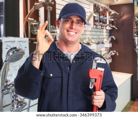 Plumber hands with a pipe wrench over plumbing tools background. - stock photo