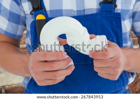 Plumber holding sink pipe on white background against red brick wall - stock photo