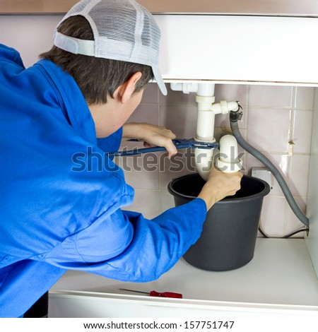 plumber in working clothes fixing a drain - stock photo