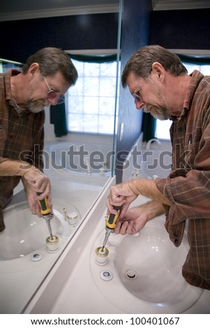 Plumber installing new faucet gaskets to save water and cut down on water bill - stock photo