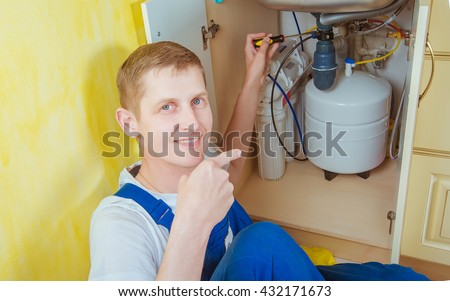 Plumber installs a water filter. water filter.  - stock photo