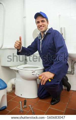 Plumber kneeling next to toilet showing thumb up in public bathroom - stock photo